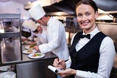 Camarera sonriente con el cuaderno de notas en cocina comercial fotos de archivo libres de regalías