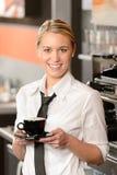 Camarera sonriente joven con la taza de café Imagen de archivo libre de regalías
