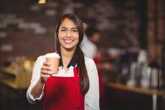 Camarera sonriente que da una taza para llevar Imágenes de archivo libres de regalías