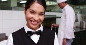 Camarera sonriente que es dada un plato por el cocinero almacen de video