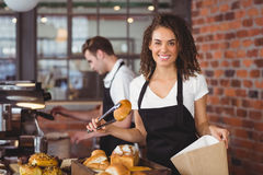 Camarera sonriente que pone el rollo de pan en bolsa de papel Imagenes de archivo