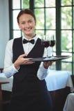 Camarera sonriente que sostiene una bandeja con los vidrios de vino rojo Fotografía de archivo