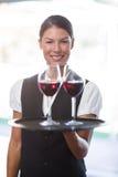 Camarera sonriente que sostiene una bandeja con los vidrios de vino rojo Foto de archivo libre de regalías