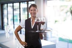Camarera sonriente que sostiene una bandeja con los vidrios de vino rojo Imágenes de archivo libres de regalías
