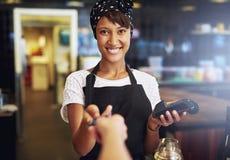 Camarera sonriente que toma una tarjeta de crédito Fotografía de archivo