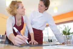 Camarera y cocinero que hablan en restaurante Imágenes de archivo libres de regalías