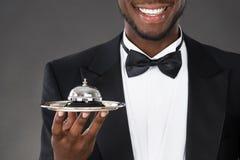 Camarero africano Holding Service Bell Imágenes de archivo libres de regalías