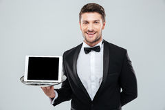 Camarero alegre en el smoking que sostiene la tableta de la pantalla en blanco en la bandeja Fotos de archivo libres de regalías