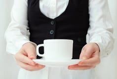 Camarero caucásico de la muchacha en la camisa blanca y el chaleco negro con pares del té en manos imágenes de archivo libres de regalías