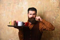 Camarero con diversas tazas de té en la bandeja Servicio y restaurante Fotos de archivo