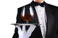 Camarero con el trago de brandy en la bandeja Foto de archivo