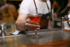 Camarero con el vidrio del cóctel sabroso en el contador en club nocturno foto de archivo