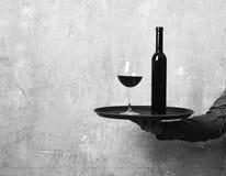 Camarero con el vidrio y la botella de vino rojo en la bandeja imágenes de archivo libres de regalías