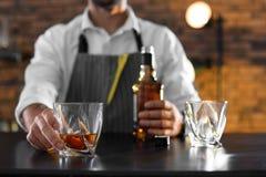 Camarero con el vidrio y la botella de whisky en el contador en la barra, primer imagenes de archivo