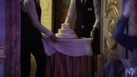 Camarero con la torta blanca de la celebración metrajes