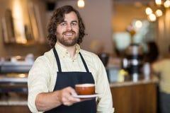 Camarero confiado Holding Coffee Cup en café Imágenes de archivo libres de regalías