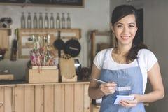 Camarero de sexo femenino asiático en orden de la escritura del delantal fotos de archivo libres de regalías