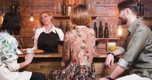 Camarero de sexo femenino feliz contratado a una conversación con sus clientes almacen de metraje de vídeo