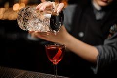 Camarero de sexo femenino profesional que vierte un alcohol transparente de la taza de cristal de medición a través del tamiz a imágenes de archivo libres de regalías