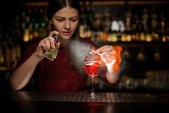Camarero de sexo femenino que asperja un vidrio de cóctel con el cóctel de la jeringuilla de Aperol con un whisky peated y que ha fotografía de archivo