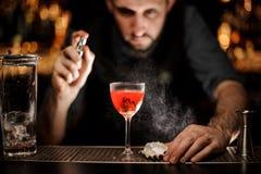 Camarero de sexo masculino que rocía en el cóctel rojo transparente delicioso en el vidrio fotografía de archivo libre de regalías