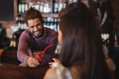 Camarero de sexo masculino que sirve una bebida del cóctel al cliente en el contador de la barra Foto de archivo