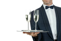 Camarero del varón adulto que sirve dos vidrios de champán aislados Imagen de archivo