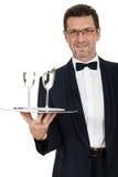 Camarero del varón adulto que sirve dos vidrios de champán aislados Fotos de archivo