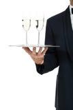 Camarero del varón adulto que sirve dos vidrios de champán aislados Fotografía de archivo