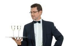 Camarero del varón adulto que sirve dos vidrios de champán aislados Imágenes de archivo libres de regalías