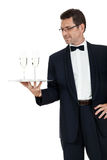 Camarero del varón adulto que sirve dos vidrios de champán aislados Foto de archivo