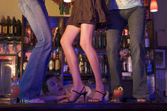 Camarero enorme en tres mujeres jovenes que bailan en barra Imagen de archivo