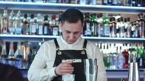 Camarero hermoso joven en cóctel de mezcla interior del alcohol de la barra almacen de video