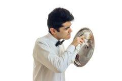 Camarero hermoso joven en una bandeja blanca de la toalla del lado de la camisa para el Cookware Fotografía de archivo libre de regalías