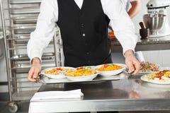 Camarero Holding Pasta Dishes en bandeja Foto de archivo libre de regalías