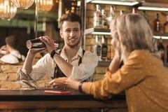 Camarero joven agradable que charla con el cliente Imagen de archivo