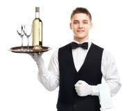 Camarero joven con la botella de vino en la bandeja Imágenes de archivo libres de regalías