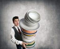 Camarero joven con una pila de placas a disposición Fotografía de archivo