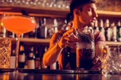camarero Oscuro-cabelludo que tiene turno de noche que hace el cóctel imagen de archivo libre de regalías