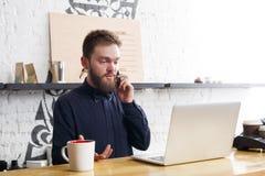 Camarero pensativo que trabaja en el ordenador portátil en el contador de la barra Fotos de archivo