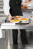 Camarero Placing Pasta Dishes en la bandeja Imagenes de archivo