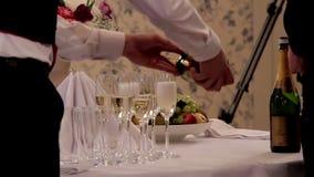 Camarero Pouring Champagne sobre los vidrios vacíos almacen de video