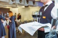 Camarero profesional en el uniforme que sostiene una bandeja con los vidrios de la vid en el evento del negocio Concepto del abas Fotografía de archivo libre de regalías