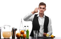 Camarero profesional que prepara una bebida con la cal o el limón, aislado en un fondo blanco Concepto del restaurante y del club Fotos de archivo
