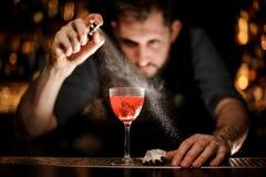 Camarero profesional que rocía en el cóctel rojo transparente delicioso en el vidrio fotografía de archivo