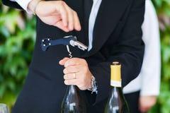 Camarero que abre una botella de vino blanco Imagen de archivo libre de regalías