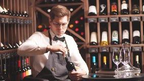 Camarero que abre una botella de vino con el sacacorchos en restaurante con los estantes del vino almacen de metraje de vídeo