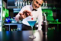 Camarero que adorna el cóctel con la cereza Imágenes de archivo libres de regalías