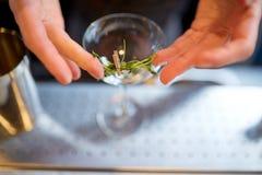Camarero que adorna el vidrio del cóctel en la barra Fotos de archivo