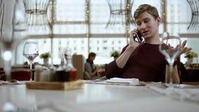 Camarero que da el menú a un hombre, almuerzo de negocios, servicio del restaurante el hombre se está sentando en un café mode almacen de video